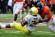 Running back Kenjon Barner #24 of the Oregon Ducks is tackled by safety Tyrequek Zimmerman #8 of the Oregon State Beavers in the first quarter of the game on November 24, 2012 at Reser Stadium in Corvallis, Oregon.