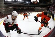 Clarke MacArthur #16 of the Ottawa Senators battles Pierre-Edouard Bellemare #78 of the Philadelphia Flyers for the puck against the boards during the first period at Wells Fargo Center on April 11, 2015 in Philadelphia, Pennsylvania.