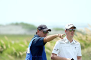 Justin Rose of England (R) and his caddie Mark Fulcher discuss a shot on the sixth tee during Round Three of the 94th PGA Championship at the Ocean Course on August 11, 2012 in Kiawah Island, South Carolina.