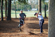 Justin Thomas of the United States plays a shot from the pine straw as caddie Jimmy Johnson looks on during practice rounds prior to THE PLAYERS Championship on the Stadium Course at TPC Sawgrass on May 9, 2018 in Ponte Vedra Beach, Florida.