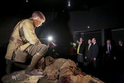 """New Zealand Prime Minister John Key and Australian Prime Minister Tony Abbott look at an exhibit with Creative Director of Weta Workshop, Sir Richard Taylor during a tour of """"Gallipoli: The scale of our war"""" exhibition at Te Papa Museum on April 20, 2015 in Wellington, New Zealand. Australian Prime Minister Tony Abbott is in Wellington today as part of commemorations ahead of the 100th anniversary of the ANZAC landings at Gallipoli."""