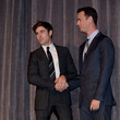 He shakes hands with Colin Hanks.