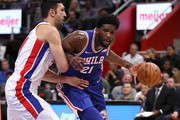 Joel Embiid #21 of the Philadelphia 76ers drives around Zaza Pachulia #27 of the Detroit Pistons during the first half at Little Caesars Arena on October 23, 2018 in Detroit, Michigan. NOTE TO USER: User expressly acknowledges and agrees that, by downloading and or using this photograph, User is consenting to the terms and conditions of the Getty Images License Agreement.