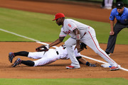 Ichiro Suzuki #51 of the Miami Marlins slides into first base under the tag of Ryan Howard #6 of the Philadelphia Phillies during the first inning of the game at Marlins Park on September 5, 2016 in Miami, Florida.