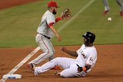 Marcell Ozuna #13 of the Miami Marlins slides into third on a triple as Andres Blanco #4 of the Philadelphia Phillies fields the throw during a game  at Marlins Park on September 7, 2016 in Miami, Florida.