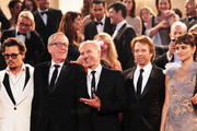 """(L-R) Actors Johnny Depp, Geoffrey Rush, guest, Jerry Bruckheimer, and Penelope Cruz depart the """"Pirates of the Caribbean: On Stranger Tides"""" premiere at the Palais des Festivals during the 64th Cannes Film Festival on May 14, 2011 in Cannes, France."""