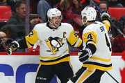 Sidney Crosby #87 of the Pittsburgh Penguins celebrates his first period goal with Justin Schultz #4 while playing the Detroit Red Wings at Little Caesars Arena on March 27, 2018 in Detroit, Michigan.