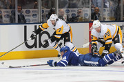 Matt Cullen #7 of the Pittsburgh Penguins slips by Morgan Rielly #44 of the Toronto Maple Leafs as Patric Hornqvist #72 of the Penguins knocks him down during an NHL game at Scotiabank Arena on October 18, 2018 in Toronto, Ontario, Canada. The Penguins defeated the Maple Leafs 3-0.