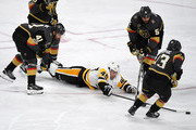 Dominik Simon #49 of the Pittsburgh Penguins dives on the ice as he tries to control the puck against Pierre-Edouard Bellemare #41, Deryk Engelland #5 and Brendan Leipsic #13 of the Vegas Golden Knights in the third period of their game at T-Mobile Arena on December 14, 2017 in Las Vegas, Nevada. The Golden Knights won 2-1.