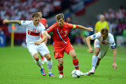 Andrey Arshavin of Russia is put under pressure by Eugen Polanski of Poland and Jakub Blaszczykowski of Poland during the UEFA EURO 2012 group A match between Poland and Russia at The National Stadium on June 12, 2012 in Warsaw, Poland.