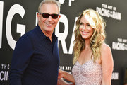 """Kevin Costner (L) and Christine Baumgartner attend the premiere of 20th Century Fox's """"The Art of Racing in the Rain"""" at El Capitan Theatre on August 01, 2019 in Los Angeles, California."""