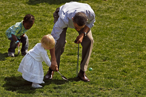 U.S. President Barack Obama helps a girl move her egg down the lawn during the Easter Egg Roll at the White House April 5, 2010 in Washington, DC.  About 30,000 people are expected to attend attended the 132-year-old tradition of rolling colored eggs down the South Lawn of the White House.