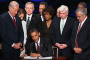 U.S. President Barack Obama signs the Dodd-Frank Wall Street Reform and Consumer Protection Act before (L-R) Vice President Joe Biden, Speaker of the House Nancy Pelosi (D-CA), Senate Majority Leader Harry Reid (D-NV), Rep. Maxine Waters (D-CA), Sen. Chris Dodd (D-CT) and Rep. Barney Frank (D-MA) at the Ronald Reagan Building July 21, 2010 in Washington, DC. The bill is the strongest financial reform legislation since the Great Depression and also creates a consumer protection bureau that oversees banks on mortgage lending and credit card practices.