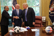 U.S. President Donald Trump (R) shakes hands with U.S. Soccer President Carlos Cordeiro (L) and FIFA President Gianni Infantino in the Oval Office at the White House August 28, 2018 in Washington, DC. The 2026 FIFA World Cup will be jointly hosted by the United States, Canada and Mexico and will be the first World Cup in history to be held in three countries at the same time.