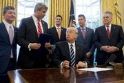 US President Donald Trump speaks with Representative Bill Huizenga (2nd L), Republican of Michigan, before signing House Joint Resolution 41, which removes some Dodd-Frank regulations on oil and gas companies, during a bill signing ceremony in the Oval Office of the White House in Washington, DC, February 14, 2017. / AFP / SAUL LOEB