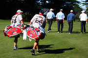 Caddies Steve Williams, (R) and Jimmy Johnson walk up a fairway with their players during a practice round prior to the start of The Presidents Cup at Harding Park Golf Course on October 7, 2009 in San Francisco, California.