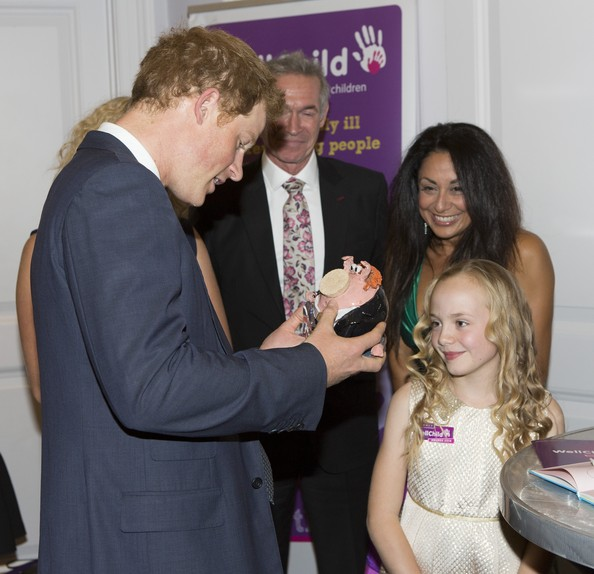 "Prince Harry Prince Harry meets Olivia Ruston, good morning britain young hero award and presents Harry with a ""Harry look-a-like"" piggy bank, during the WellChild awards at the London Hilton on September 22, 2014 in London, England."