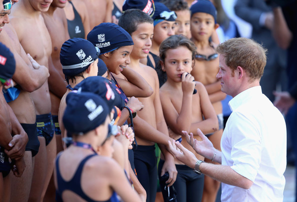 Prince Harry presents medals to young swimmers during a visit to Minas Tenis Clube on June 24, 2014 in Belo Horizonte, Brazil.  Prince Harry is on a four day tour of Brazil that will be followed by Two days in Chile.