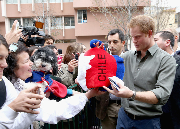 Prince Harry is presented with a Chile 'Beer hat' as he meets members of the public outside Valpariso Firestation on June 28, 2014 in Valpariso, Chile. Firefighters from Valpariso were involved in dealing with the devastating forest fires that hit the area in April. Prince Harry is on a three day tour of Chile after visiting Brazil.