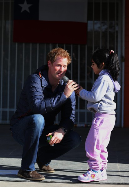 Pascal Vasquez, 7, steals the microphone from Prince Harry as he meets children with mental and physical disabilities at the Fundacion Amigos de Jesus on June 29, 2014 in Santiago, Chile.  Prince Harry is on the final day of a three day tour of Chile after visiting Brazil.