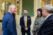 Prince Charles, Prince of Wales speaking with artist Gareth Reid (2nd L) during a reception at Hillsborough Castle on April 9, 2019 in Belfast, Northern Ireland.