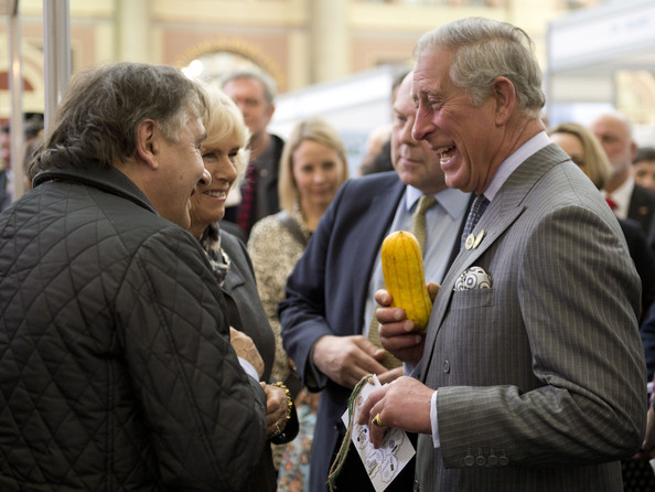 Camilla, Duchess of Cornwall and Prince Charles, Prince of Wales share a joke as Raymond Blanc looks on as the Duchess holds a squash during The Edible Garden Show at Alexandra Palace on March 28, 2014 in London, England.