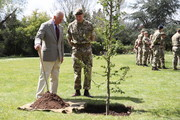 Prince Charles, Prince of Wales helps plant a tree next to Commanding Officer, Lieutenant Colonel Henry Llewelyn-Usher, during a visit to the Welsh Guards at Combermere Barracks on May 5, 2021 in Windsor, England.