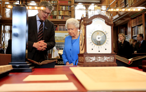 Queen Elizabeth II is shown items from the George III Collection pertaining to science and the Arts, including the 1765 Eardley Norton clock by Royal Librarian Oliver Urquhart Irvine (L) while attending the launch of the George III Project at an event held in the Royal Library in Windsor Castle on April 1, 2015 in Windsor, England.