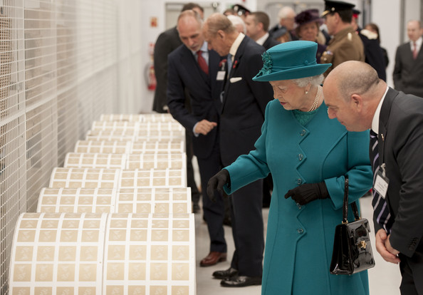 Queen Elizabeth II  examines large rolls of stamps during an official visit to International Security Printers to view their work on specialist postage stamps on October 30, 2014 in Wolverhampton, England.