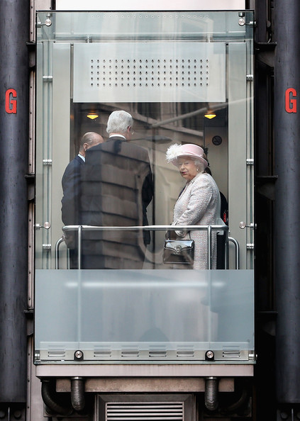 Queen Elizabeth II travels in the lifts in the Richard Rogers designed Lloyds of London Building as she leaves on March 27, 2014 in London, England.
