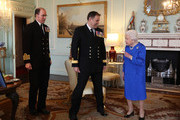 Queen Elizabeth II receives Commodore Steven Moorhouse (centre, outgoing Commanding Officer, HMS Queen Elizabeth) and Captain Angus Essenhigh (incoming Commanding Officer), during a private audience in the Queens Private Audience Room in Buckingham Palace on March 18, 2020 in London, England.