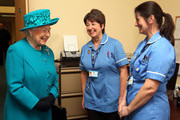 Queen Elizabeth II meets nurses Sarah Wallis and Daniela Reynolds (R) during a visit to The Norfolk Hospice at Hillington on February 4, 2016 near King's Lynn, England. The Queen met patients, trustees, volunteers and medical professionals working at the hospice, which has been serving its local community close to her Sandringham Estate for over 30 years.