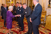 Queen Elizabeth II meets President of the Rugby Football Union Jason Leonard (second right) and Chairman of World Rugby Bernard Lapasset (right) at a Rugby World Cup reception at Buckingham Palace on October 12, 2015 in London, United Kingdom.