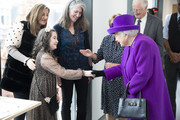 Queen Elizabeth II meets Lily Conkan, aged 8, who is having braces fitted, as she opens the new premises of the Royal National ENT and Eastman Dental Hospital on February 19, 2020 in London, England.