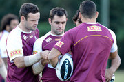 (L-R) Nate Myles, Cameron Smith, Greg Inglis and Johnathan Thurston read the coach's training instructions during a Queensland Maroons State of Origin training session at  Palmer Resort Coolum on May 29, 2013 in Brisbane, Australia.