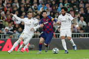 Lionel Messi of FC Barcelona controls the ball while challenged by Sergio Ramos of Real Madrid and Marcelo of Real Madrid during the Liga match between Real Madrid CF and FC Barcelona at Estadio Santiago Bernabeu on March 01, 2020 in Madrid, Spain.
