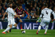 Neymar of Barcelona takes on Pepe and Sergio Ramos of Real Madrid during the La Liga match between Real Madrid CF and FC Barcelona at the Bernabeu on March 23, 2014 in Madrid, Spain.