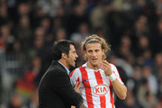 Atletico Madrid manager Quique Sanchez Flores has a word with Diego Forlan during the La Liga match between Real Madrid and Atletico Madrid at Estadio Santiago Bernabeu on November 7, 2010 in Madrid, Spain.
