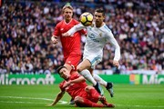 Real Madrid's Portuguese forward Cristiano Ronaldo (R) challenges Sevilla's French defender Clement Lenglet (C) and Sevilla's Danish defender Simon Kjaer (back) during the Spanish league football match between Real Madrid and Sevilla at the Santiago Bernabeu Stadium in Madrid on December 9, 2017. / AFP PHOTO / PIERRE-PHILIPPE MARCOU