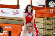 Founder and President of Virgin Group Sir Richard Branson carries burlesque artist Dita Von Teese on his shoulders after helping her down from a lift as they pose with a Virgin Atlantic Airways 747-400 aircraft at McCarran International Airport June 15, 2010 in Las Vegas, Nevada. Branson is celebrating his British airline's 10th anniversary of flying between London and Las Vegas.
