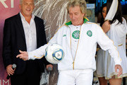 """Co-CEO and President of AEG Live/Concerts West John Meglen (L) looks on as recording artist Rod Stewart kicks a soccer ball to the crowd as he is introduced at Caesars Palace to launch his two-year residency """"Rod Stewart: The Hits."""" at The Colosseum August 24, 2011 in Las Vegas, Nevada."""