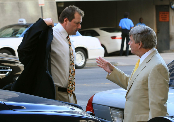 Baseball pitching star Roger Clemens (L) puts on his coat as he arrives at the U.S. District Court, on August 30, 2010 in Washington, DC.