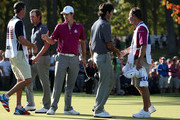 Webb Simpson and Bubba Watson greet Justin Rose of Europe on the 14th green after the team of Simpson/Watson defeated the team of Rose/Molinari 5&4 during day two of the Afternoon Four-Ball Matches for The 39th Ryder Cup at Medinah Country Club on September 29, 2012 in Medinah, Illinois.