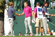 Ian Poulter of Europe (C) shakes hands with Webb Simpson of the USA on the 18th green after the Rose/Poulter team defeated the Simpson/Watson team 1up during day two of the Morning Foursome Matches for The 39th Ryder Cup at Medinah Country Club on September 29, 2012 in Medinah, Illinois.