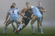 Andy Powell of Sale Sharks is tackled by Mark Sorenson and Calum Clark of Northampton Saints during the Aviva Premiership match between Sale Sharks and Northampton Saints at Salford City Stadium  on November 30, 2012 in Salford, England.