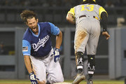 Clayton Kershaw #22 of the Los Angeles Dodgers is tagged out at second base by Freddy Galvis #13 of the San Diego Padres when he tried to stretch a single into a double in the seventh inning at Dodger Stadium on August 25, 2018 in Los Angeles, California. All players across MLB will wear nicknames on their backs as well as colorful, non-traditional uniforms featuring alternate designs inspired by youth-league uniforms during Players Weekend.