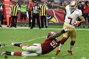 Quarterback Colin Kaepernick #7 of the San Francisco 49ers breaks a tackle by linebacker Alex Okafor #57 of the Arizona Cardinals in the third quarter of the NFL game at University of Phoenix Stadium on September 27, 2015 in Glendale, Arizona.
