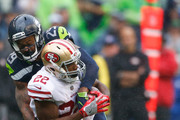 Running back Matt Breida #22 of the San Francisco 49ers is tackled by free safety Earl Thomas #29 of the Seattle Seahawks during the second half of the game at CenturyLink Field on September 17, 2017 in Seattle, Washington.