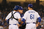 Pitching coach Rick Honeycutt of the Los Angeles Dodgers visits the mound to talk to pitcher Josh Beckett #61 as catcher A.J. Ellis #17 looks on during the MLB game against the San Francisco Giants in the fourth inning at Dodger Stadium on April 3, 2013 in Los Angeles, California.