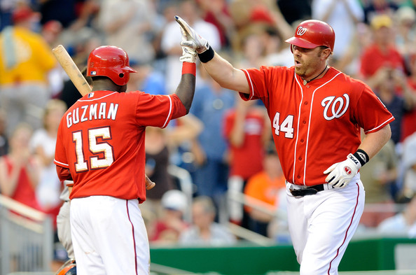 Adam Dunn #44 of the Washington Nationals is congratulated by teammate Cristian Guzman #15 after hitting a home run in the fourth inning against the San Francisco Giants at Nationals Park on July 9, 2010 in Washington, DC.